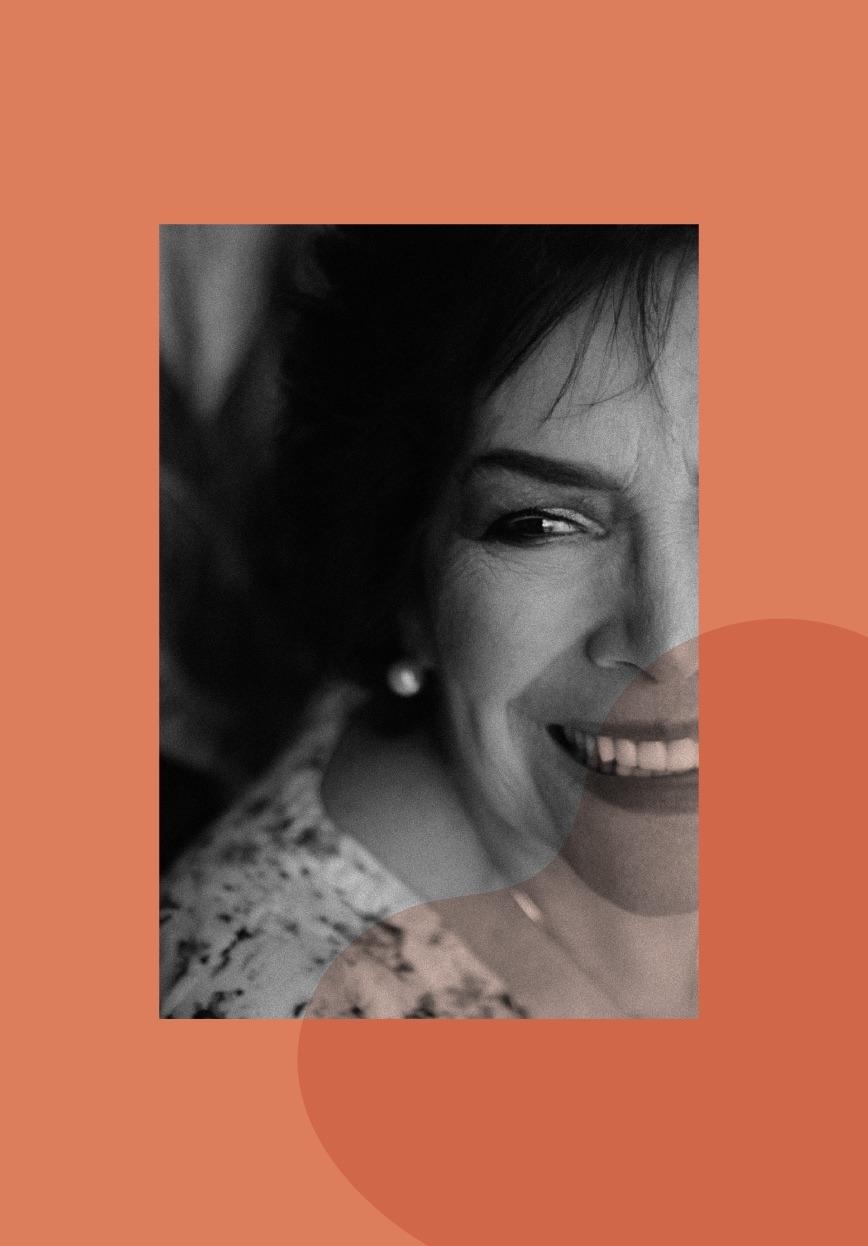 photo en noir et blanc sur fond orange d'une femme d'âge mûr qui sourit. La photo illustre la cure de bien-être ménopause que propose la luxopuncture